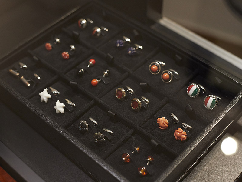 An     array of Barbarulo cufflinks in various shapes, colours and materials, set out neatly in a black display     case.